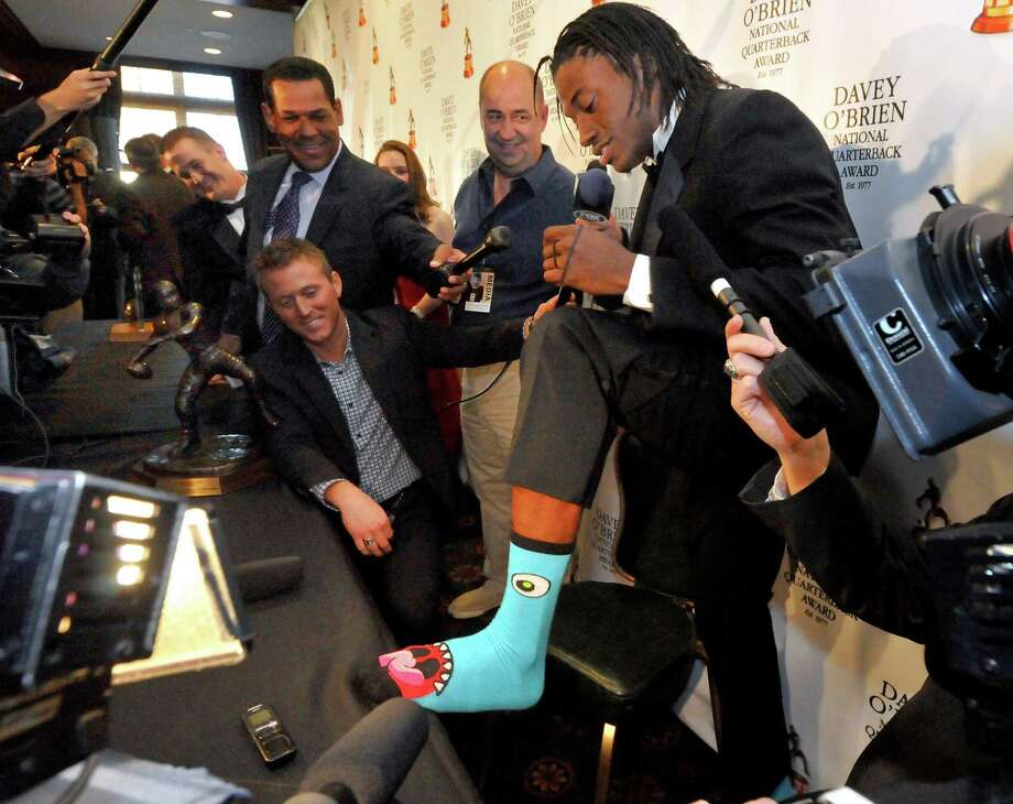 Former Baylor quarterback Robert Griffin III shows off his monster socks during a news conference in Fort Worth, Texas, Monday, Feb. 20, 2012, at the Davey O'Brien Award dinner. (AP Photo/Forth Worth Star-Telegram, Max Faulkner) MAGS OUT Photo: Max Faulkner, MBR / Fort Worth Star-Telegram