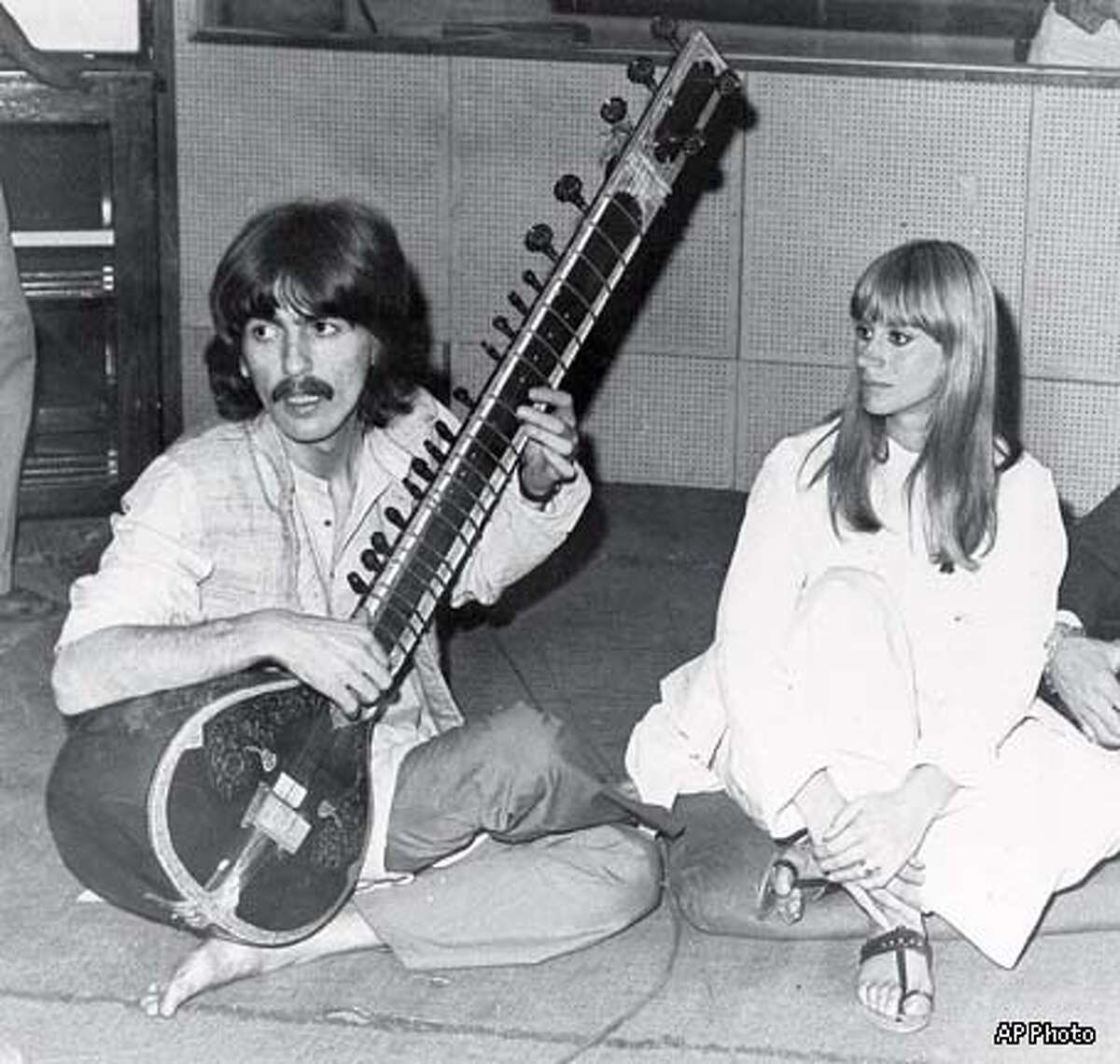 FILE--George Harrison plays the sitar in Bombay, India in this Jan. 14, 1968, file photo. Harrison died Thursday Nov. 29, 2001, a longtime family friend said. He was 58. At right is British actress Rita Tushingham, who was making a motion picture in India. (AP Photo)