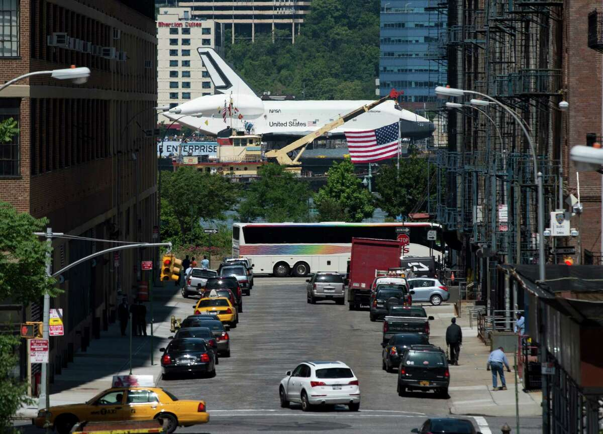 The Space Shuttle Enterprise makes its way up the Hudson River past a busy street as it is towed to the Intrepid Museum on a barge Wednesday in New York. Enterprise was moved by barge to the Intrepid Sea, Air and Space Museum in New York where it will be permanently displayed. (DON EMMERT/AFP/GettyImages)
