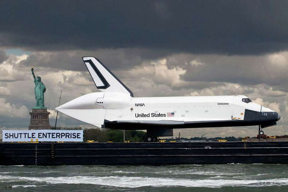 NEW YORK, NY - JUNE 06:  The space shuttle Enterprise is brought past the Statue of Liberty on a barge on June 6, 2012 in New York City. The shuttle is on it's way to the USS Intrepid, where it be on display for viewing by the general public. NASA's space shuttle program came to an end in August, 2011, after 30 years of service. Photo: Andrew Burton, Getty Images / 2012 Getty Images