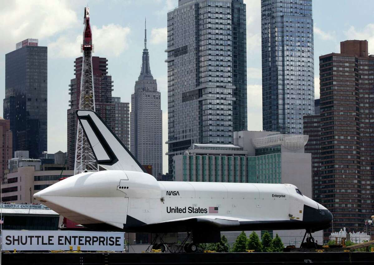 The space shuttle Enterprise makes the final leg of its journey to its new Manhattan home on the flight deck of the Intrepid Sea, Air & Space Museum. Wednesday. The U.S. space agency, NASA, ended its shuttle program last year. (AP Photo/Richard Drew)