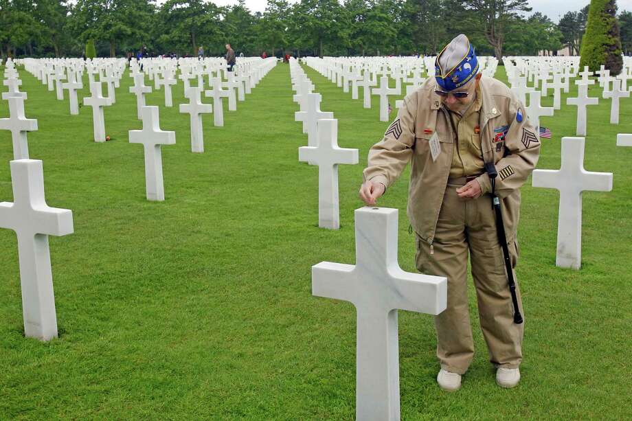U.S. WW II veteran Clarence  Mac Evans, 87, from West Virginia, who landed in Normandy on June 6, 1944, with the 29th infantery division, puts a coin on the tomb of  fellow Franck Nuzzo, from the 29th division who died on June 6, 1944,  at the Colleville American military cemetery.(AP Photo/Remy de la Mauviniere) Photo: Remy De La Mauviniere, Associated Press / AP