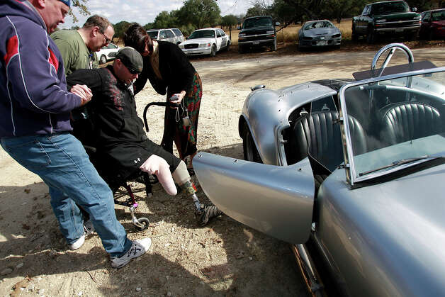 Wounded Army soldier Nick McCoy gets help out of a 1966 replica Cobra after going for ride with owner Ron Martel of Houston (far left) on December 13, 2008. McCoy served in the U.S. Army in Southern Iraq when he was wounded in December of 2006. McCoy joined other soldiers as part of Operation Comfort's Automotivation program that offers an opportunity for soldiers to work on vehicles as part of their recovery and therapy from their injuries. On this particular day, club members from various Cobra replica associations in Texas drove their vehicles to South San Antonio to offer rides and give gifts of appreciation to the soldiers. Kin Man Hui/kmhui@express-news.net Photo: Kin Man Hui, San Antonio Express-News / San Antonio Express-News
