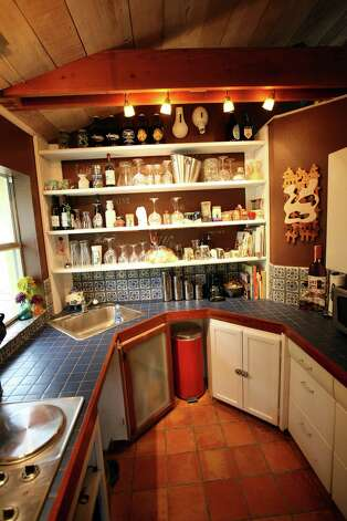 The Millers painted their small kitchen chocolate and used white paint on the open shelves. Their cats like to walk around on the exposed upper beams. Photo: Danny Warner