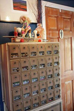 Old post office boxes are small storage spaces in the master bedroom. A piece made by James, called Moustache Ride is atop the boxes. He made the piece for his grandfather, using some of his grandfatherÕs shaving brushes. Photo: Danny Warner
