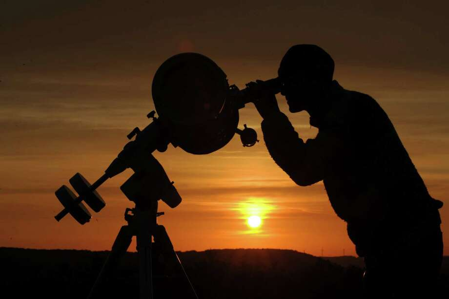 A hobby astronomer points his telescope at the yello disk of the rising sun as he observes the transit of planet Venus in Ziegenhain near Jena, eastern Germany, on June 6, 2012. The event, only to be seen again in 105 years, began shortly after 2200 GMT on Tuesday, visible first from the Pacific and north and central Americas as a small black dot trailing across the solar surface. Photo: ANGELIKA WARMUTH, AFP/Getty Images / DPA
