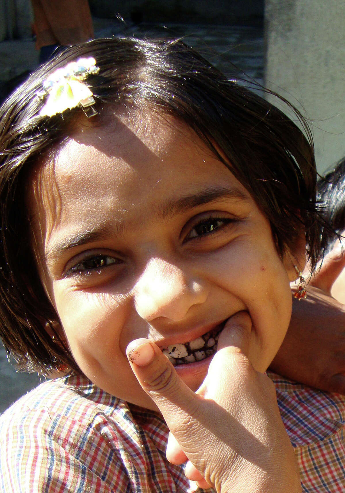 Sushmitha polishes her teeth with charcoal one day in late December. A previous volunteer gave toothbrushes and toothpaste to all of the girls at the Josephnagar boarding house, which they used in conjunction with this -- more traditional -- method.