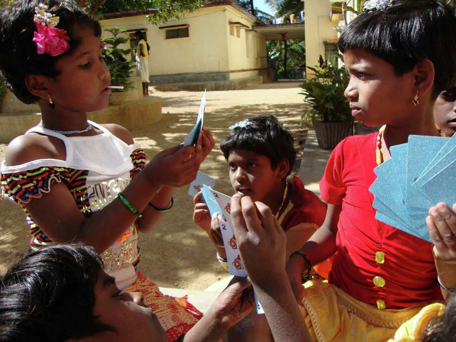 Indian girls face off during a game of Go Fish on Christmas morning outside a boardinghouse in Josephnagar, India. Photo: Lindsay Kastner, San Antonio Express-News / San Antonio Express-News