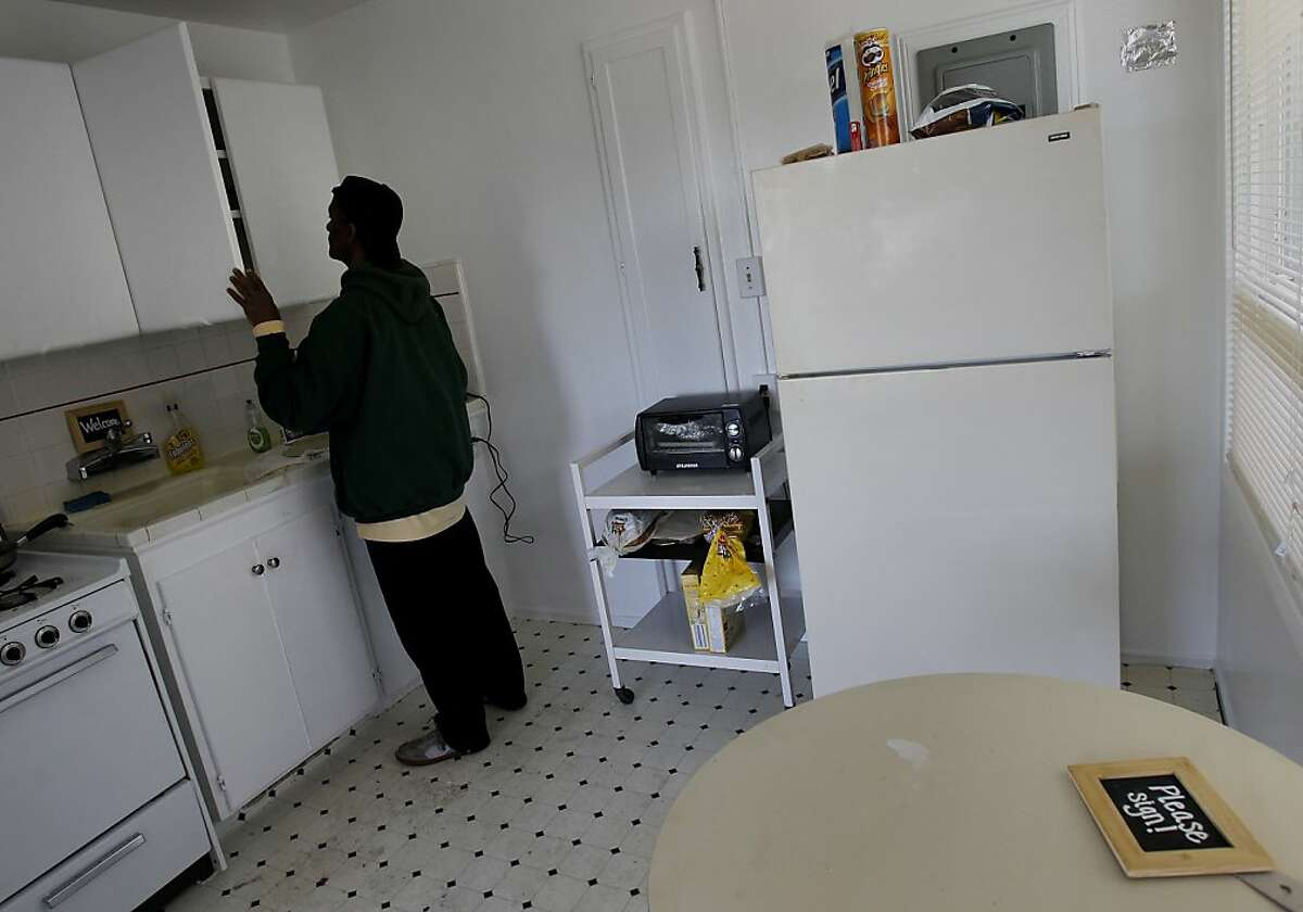 Brett Smith searches for a water glass in his apartment. Brett Smith, a U.S. Army veteran, was homeless in San Francisco for years, but now has a place in the Richmond district not far from the beach.