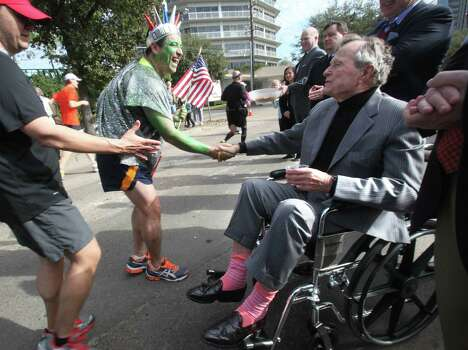 (Center) Antonio Lopez-Perla shakes hands with Former President George H. W. Bush in front of St. Martin's Episcopal Church near the 19th mile marker along Woodway Blvd. during the Chevron Houston Marathon on Sunday, Jan. 15, 2012, in Houston. ( Mayra Beltran / Houston Chronicle ) Photo: Mayra Beltran / © 2011 Houston Chronicle