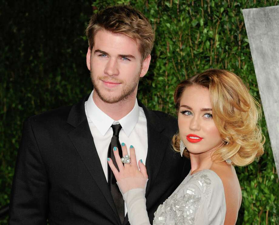 """FILE - This Feb. 26, 2012 file photo shows Miley Cyrus, right, and Liam Hemsworth at the Vanity Fair Oscar party in West Hollywood, Calif. The couple who met on the set of the movie """"The Last Song"""" in 2009 announced their engagement Wednesday morning. Publicist Jeff Raymond confirms a People Magazine report of the news. Hemsworth, the 22-year-old Australian star of """"The Hunger Games,"""" and Cyrus, the 19-year-old """"Hannah Montana"""" star and singer, were engaged on May 31. Hemsworth proposed with a 3.5-carat diamond ring, People reports. Photo: AP"""