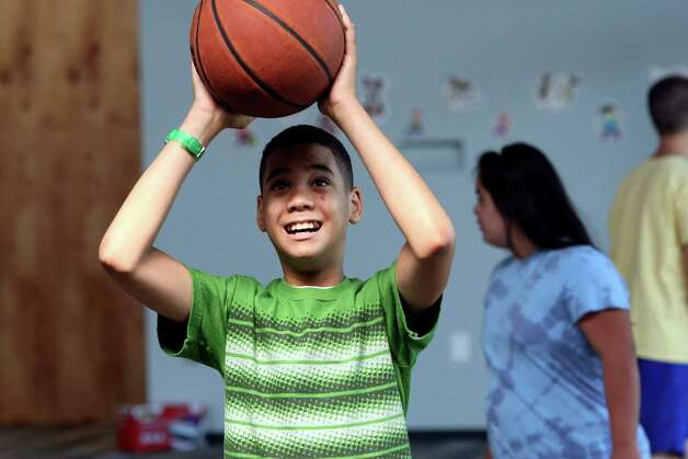 "Blair Blacksmith shoots hoops. Special Reach board member Greg Kinney says of the day camp volunteers: ""I'm amazed at the spirit of the people here."" Photo: Helen L. Montoya, San Antonio Express-News / ©SAN ANTONIO EXPRESS-NEWS"