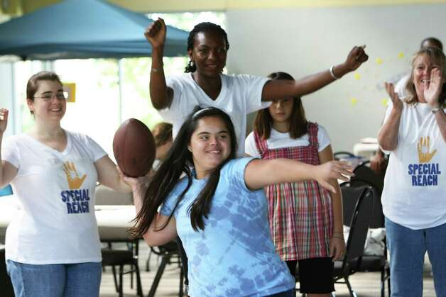 Macarena Velasquez tosses a football with former NFL quarterback Tommy Kramer during Special Reach's day camp. The nonprofit is hosting camp for kids with special needs at Crown of Life Lutheran Church. Photo: Helen L. Montoya, San Antonio Express-News / ©SAN ANTONIO EXPRESS-NEWS