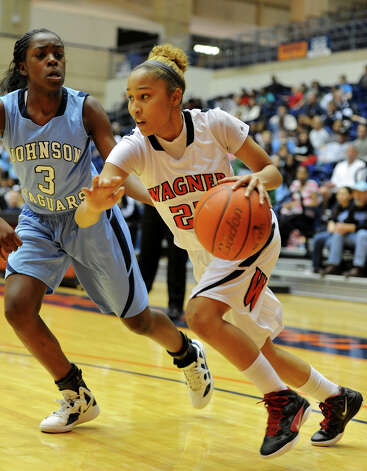 Wagner's Adriane Davis drives to the baseline past Johnson's Erica Sanders (3) during a UIL 5A girls bidistrict playoff game at the UTSA Convocation Center on Feb. 13, 2012. Photo: John Albright / For The Express-News