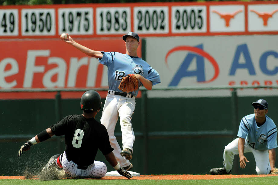 Sweeny senior 2nd baseman Michael Ferrel (#12) turns a double play against West baserunner Justin Sepeda (#8) after taking a flip from teammate and junior shortstop Jordan Limas, right, to end the top of the 7th inning in the Bulldog's 10-3 loss to the Trojans in their Class 3A state semifinal matchup at UFCU Disch-Falk Field in Austin on Wednesday. Photo: Jerry Baker, For The Chronicle