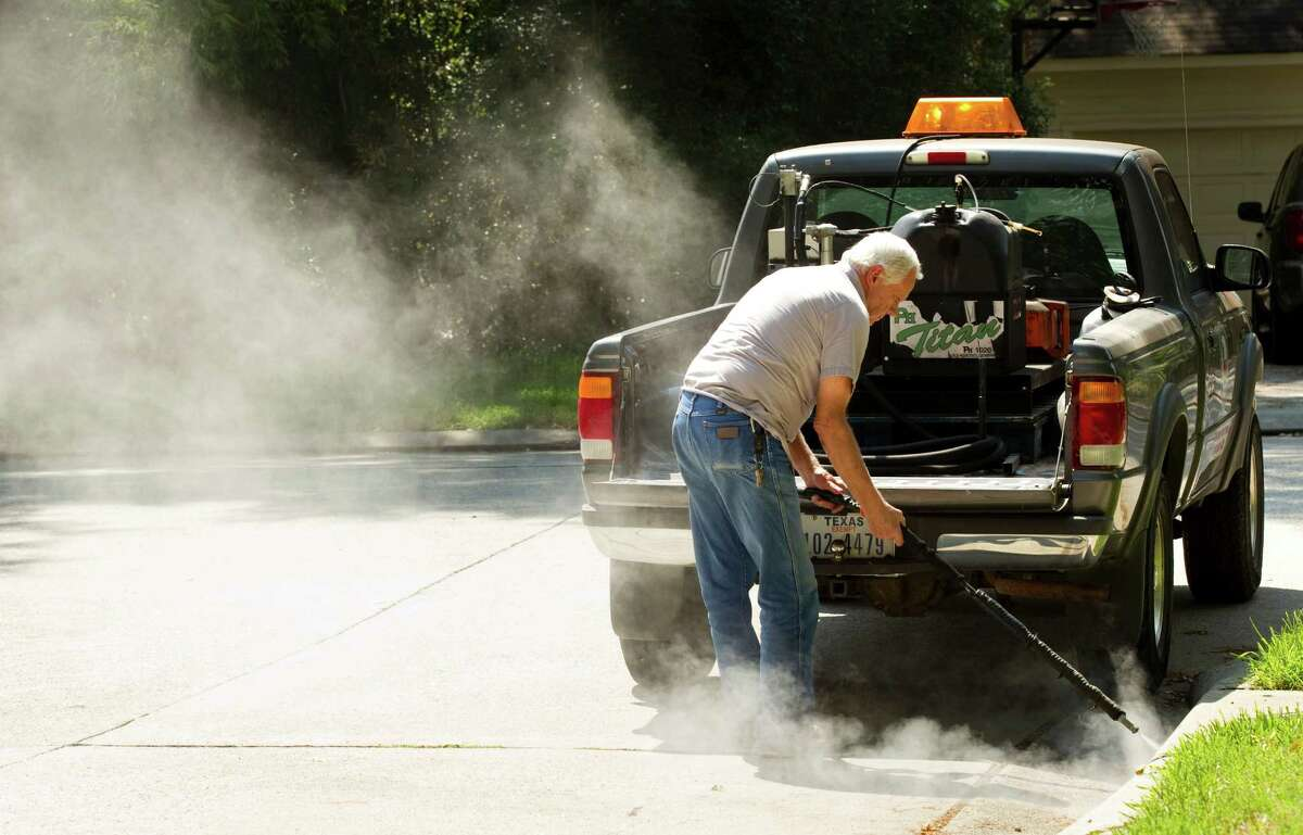 Paul Culbertson, of Montgomery County Precinct 3, sprays a storm drain Wednesday to fight mosquitoes.