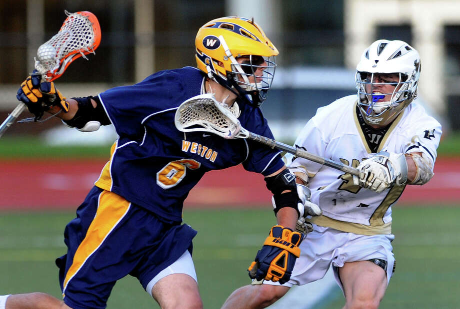 Weston's #6 Jack Scheufele, left, drives the ball behind the goal as Joel Barlow's #34 Peter Meehan defends, during boys lacrosse Class S Semifinals action in Fairfield, Conn. on Wednesday June 6, 2012. Photo: Christian Abraham / Connecticut Post