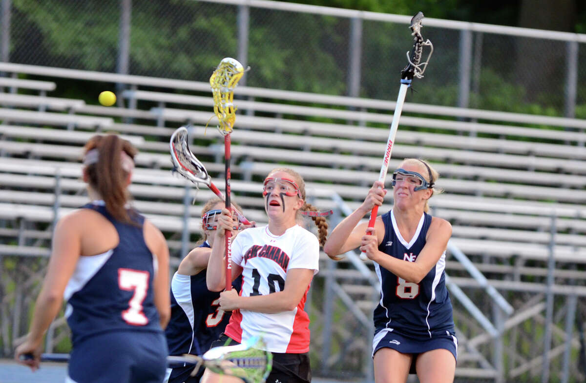 New Canaan's Sarah Mannelly (10) takes a shot as New Fairfield's Brittany Muratore (3) and Dana Bouwman (8) defend during the girls lacrosse Class M semifinals at Bunnell High School in Stratford on Wednesday, June 6, 2012.