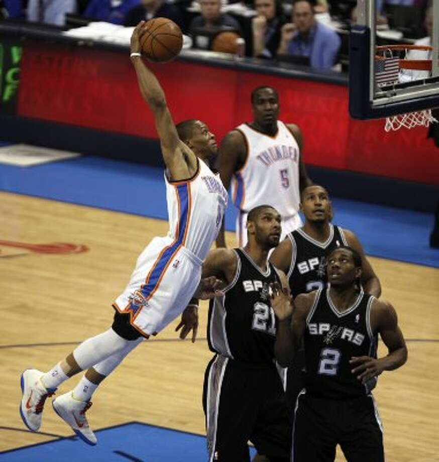 Oklahoma City Thunder's Russell Westbrook (0) dunks over San Antonio Spurs' Tim Duncan (21) and San Antonio Spurs' Kawhi Leonard (2) during the first half of game six of the NBA Western Conference Finals in Oklahoma City, Okla. on Wednesday, June 6, 2012. (Kevin Martin / San Antonio Express-News)
