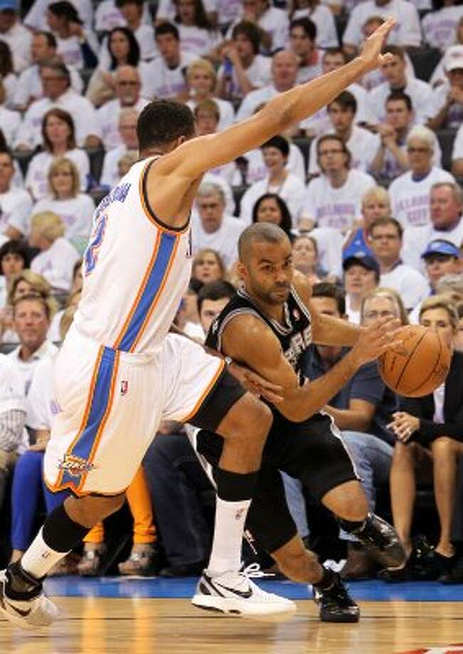 San Antonio Spurs' Tony Parker (9) drives around Oklahoma City Thunder's Thabo Sefolosha (2) during the first half of game six of the NBA Western Conference Finals in Oklahoma City, Okla. on Wednesday, June 6, 2012. (Kin Man Hui / San Antonio Express-News)