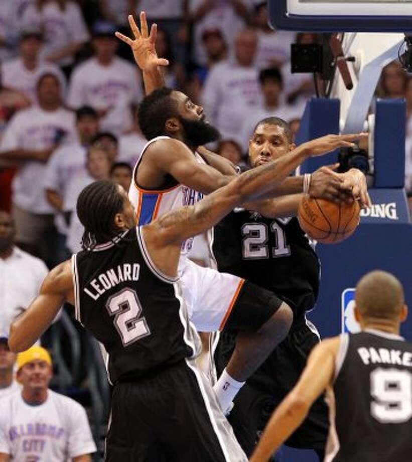 Oklahoma City Thunder's James Harden (13) drives against San Antonio Spurs' Tim Duncan (21) and San Antonio Spurs' Kawhi Leonard (2) during the first half of game six of the NBA Western Conference Finals in Oklahoma City, Okla. on Wednesday, June 6, 2012. (Kin Man Hui / San Antonio Express-News)