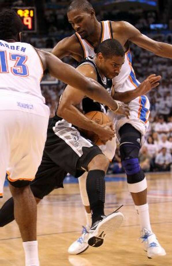 San Antonio Spurs' Gary Neal (14) drives against Oklahoma City Thunder's Kevin Durant (35) and Oklahoma City Thunder's James Harden (13) during the first half of game six of the NBA Western Conference Finals in Oklahoma City, Okla. on Wednesday, June 6, 2012. (Kin Man Hui / San Antonio Express-News)