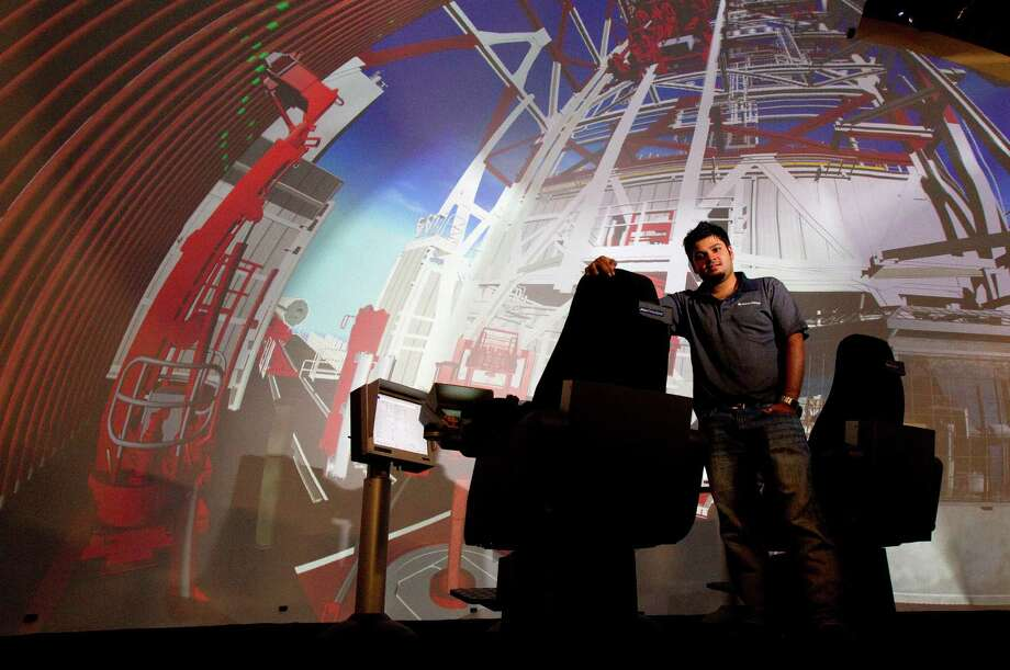 Electrical/instrumentation instructor Manas Goyal demonstrates a dome simulator at Aker Solutions' training facility in Katy. The device allows students to practice operating rig equipment in an environment that looks like a real drilling rig. Photo: Cody Duty / © 2011 Houston Chronicle