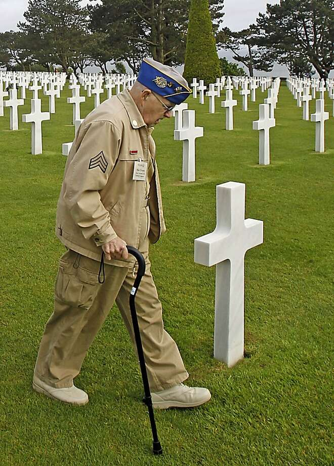 U.S. WW II veteran Clarence  Mac Evans, 87, from West Virginia, who landed in Normandy on June 6, 1944, with the 29th infantary division, walks among the graves at the Colleville American military cemetery, in Colleville sur Mer, western France, Wednesday  June 6, 2012, before the start of the ceremony commemorating the 68th anniversary of the D-Day. Clarence MacEvans is searching for the graves of 17 of his fellows who died on  D Day.(AP Photo/Remy de la Mauviniere) Photo: Remy De La Mauviniere, Associated Press