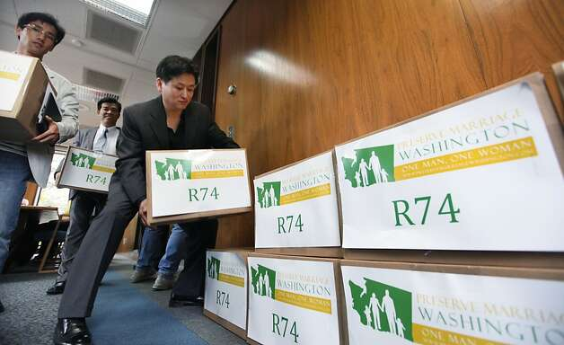 Supporters stack boxes of petitions for Referendum 74 along a wall in the Secretary of State's office to stop Washington's gay marriage law Wednesday, June 6, 2012, in Olympia, Wash. The law was blocked from taking effect as opponents filed more than 200,000 signatures seeking a public vote on the issue in November. Preserve Marriage Washington submitted the signatures just a day before the state was to begin allowing same-sex marriages. State officials will review the filings over the next week to determine whether the proposed referendum will qualify for a public vote, though the numbers suggest the measure will make the ballot easily. (AP Photo/Elaine Thompson) Photo: Elaine Thompson, Associated Press