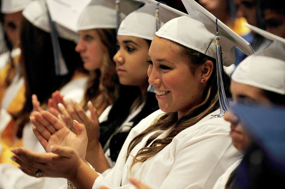 Victoria Mathews, right, claps during the Immaculate High School graduation at Church of St. Mary in Bethel, Conn., on Wednesday, June 6, 2012. Photo: Jason Rearick / The News-Times