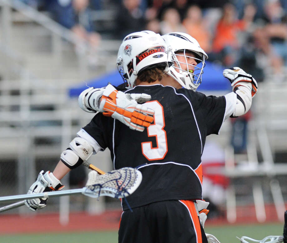 Ridgefield's Sean Riley # 3 celebrates with a teammate after Riley scored during the first half of the boys high school lacrosse state Class L semifinal between Ridgefield High School and Newtown High School at Brien McMahon High School in Norwalk, Wednesday, June 6, 2012. Photo: Bob Luckey / Greenwich Time