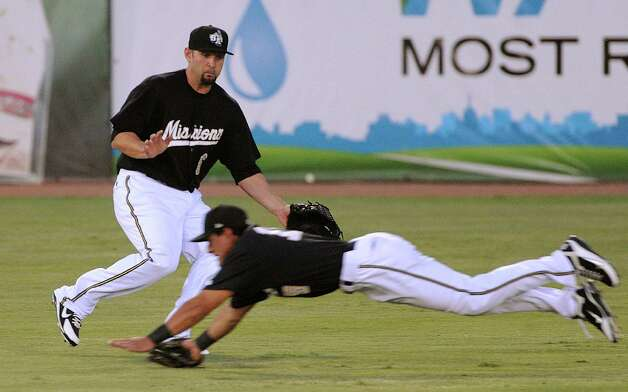 Missions left fielder Jake Blackwood watches for the ball as center fielder Reymond Fuentes unsuccessfully dives for it during Texas League action against Frisco at Wolff Stadium on Wednesday, June 6, 2012. Photo: Billy Calzada, San Antonio Express-News / © 2012 San Antonio Express-News