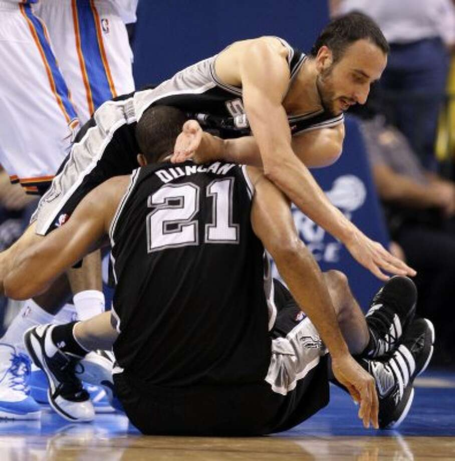San Antonio Spurs' Manu Ginobili (20) falls over San Antonio Spurs' Tim Duncan (21) during the first half of game six of the NBA Western Conference Finals in Oklahoma City, Okla. on Wednesday, June 6, 2012. (Jerry Lara / San Antonio Express-News)