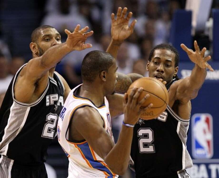 Oklahoma City Thunder's Kevin Durant (35) is guarded by San Antonio Spurs' Tim Duncan (21) and San Antonio Spurs' Kawhi Leonard (2) during the second half of game six of the NBA Western Conference Finals in Oklahoma City, Okla. on Wednesday, June 6, 2012. (Jerry Lara / San Antonio Express-News)