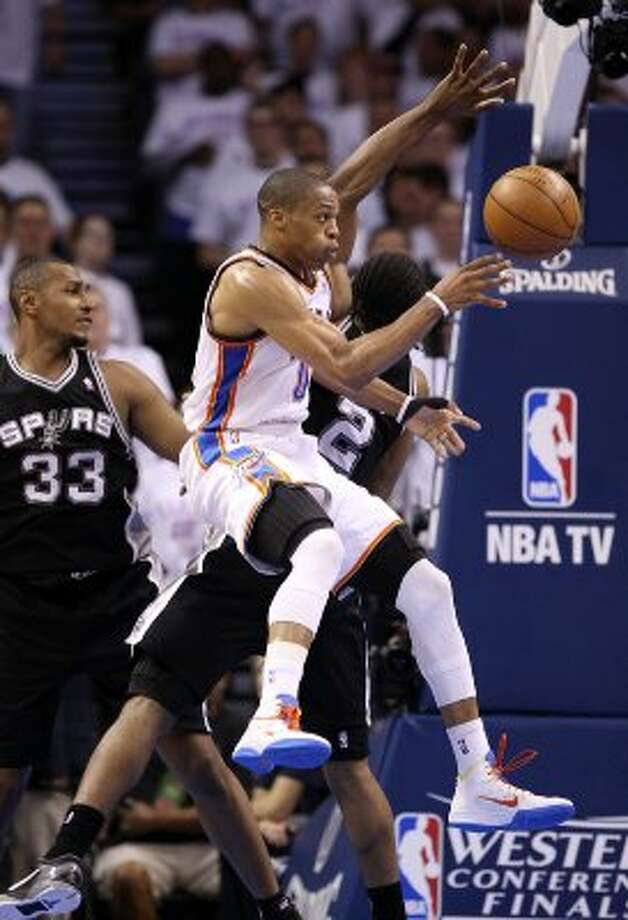 Oklahoma City Thunder's Russell Westbrook (0) passes around San Antonio Spurs' Kawhi Leonard (2) during the second half of game six of the NBA Western Conference Finals in Oklahoma City, Okla. on Wednesday, June 6, 2012. (Jerry Lara / San Antonio Express-News)