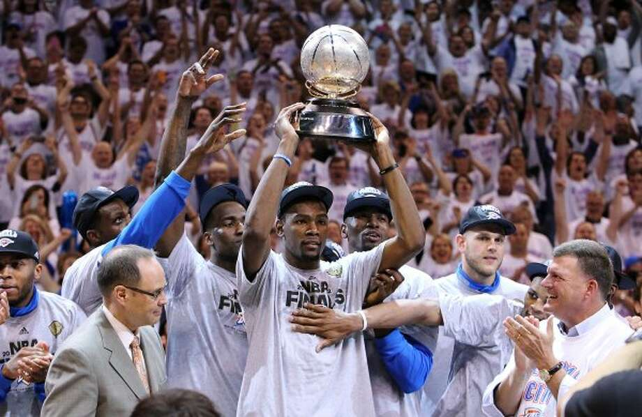 Thunder's Kevin Durant raises the Western Conference Champion trophy while the rest of the team celebrates in Oklahoma City, Okla. on Wednesday, June 6, 2012.  The Thunder won 107-99. (Kin Man Hui / San Antonio Express-News)