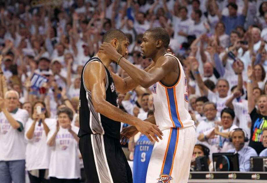 Spurs' Tim Duncan (left) gives a hug to Thunder's Kevin Durant in the closing moments of Game 6 of the NBA Western Conference Finals in Oklahoma City, Okla. on Wednesday, June 6, 2012.  The Thunder won 107-99. (Kin Man Hui / San Antonio Express-News)