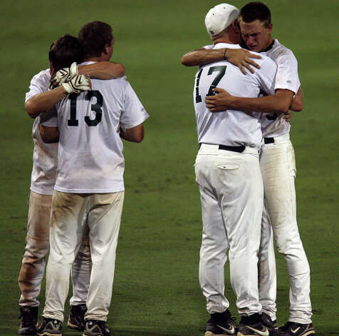 Reagan's Jordan Mengele (20) hugs Diego Flores (13) as Casey Selsor (5) hugs coach Chans Chapman after losing in the 5A Regional Finals to Lardeo United 5-4 in the third game at Whataburger Field in Corpus Christi on May 30, 2008. Photo: Express-News File Photo / delopez@express-news.net