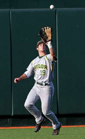 Baylor's Logan Vick pulls in a long fly ball against Texas at Disch-Falk Field in Austin on May 18, 2012. Photo: TOM REEL, San Antonio Express-News / San Antonio Express-News