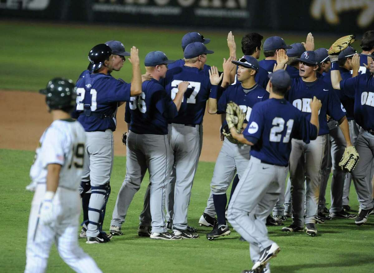 Baylor's Logan Vick (left) walks back to the dugout as Oral Roberts players celebrate after their 4-2 win after an NCAA college baseball tournament regional game on June 1, 2012, in Waco.