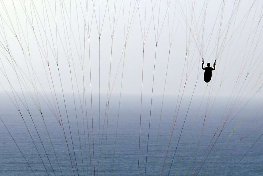 A man paraglides behind the lines of another paraglider off the Torrey Pines Gliderport  Wednesday, June 6, 2012, in San Diego. (AP Photo/Gregory Bull) Photo: Gregory Bull, Associated Press
