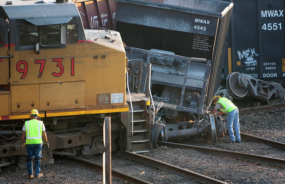 Crews work the scene of a train accident after cars derailed at the intersection of Liberty Road and N Wayside Drive Thursday, June 7, 2012, in Houston. Photo: Cody Duty, Houston Chronicle / © 2011 Houston Chronicle