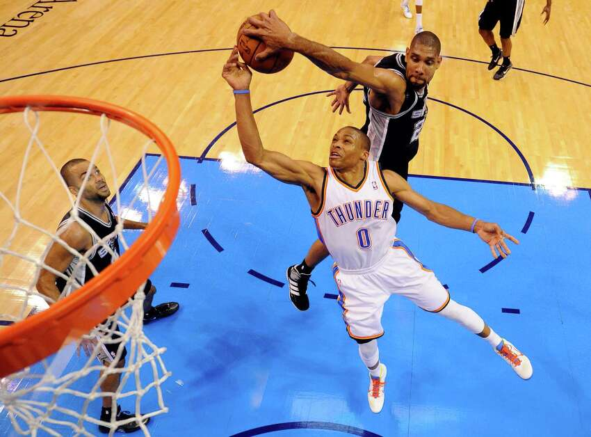 OKLAHOMA CITY, OK - MAY 31: Russell Westbrook #0 of the Oklahoma City Thunder goes up for the shot as Tim Duncan #21 of the San Antonio Spurs attempts to block it from behind in the first half in Game Three of the Western Conference Finals of the 2012 NBA Playoffs at Chesapeake Energy Arena on May 31, 2012 in Oklahoma City, Oklahoma. NOTE TO USER: User expressly acknowledges and agrees that, by downloading and or using this photograph, User is consenting to the terms and conditions of the Getty Images License Agreement.