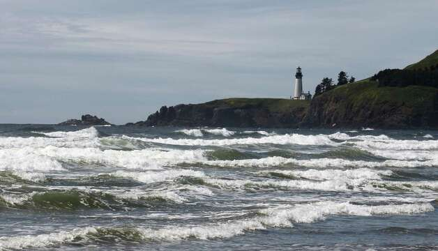 Yaquina Head Lighthouse is shown near where a massive dock washed ashore on Agate Beach Wednesday in Newport, Ore.  A nearly 70-foot-long dock that floated ashore on an Oregon beach was torn loose from a fishing port in northern Japan by last year's tsunami and drifted across thousands of miles of Pacific Ocean, a Japanese Consulate official said Wednesday. Photo: Ap