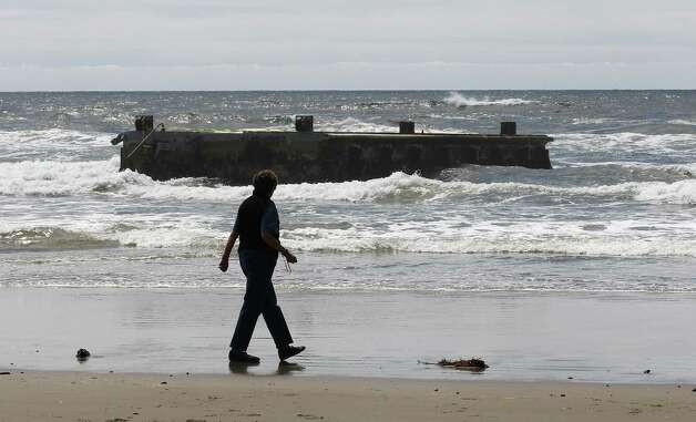 A woman looks at the massive dock that washed ashore on Agate Beach Wednesday in Newport, Ore.  A nearly 70-foot-long dock that floated ashore on an Oregon beach was torn loose from a fishing port in northern Japan by last year's tsunami and drifted across thousands of miles of Pacific Ocean, a Japanese Consulate official said Wednesday. Photo: Ap