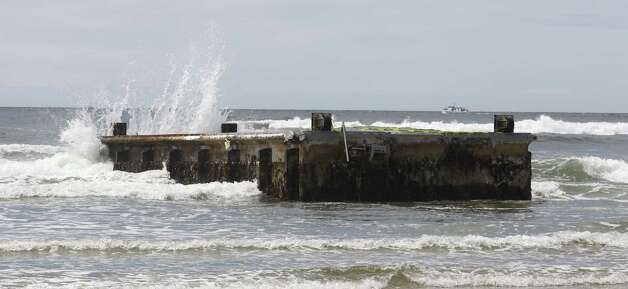 The surf pounds against the massive dock that washed ashore on Agate Beach Wednesday in Newport, Ore.  A nearly 70-foot-long dock that floated ashore on an Oregon beach was torn loose from a fishing port in northern Japan by last year's tsunami and drifted across thousands of miles of Pacific Ocean, a Japanese Consulate official said Wednesday. Photo: Ap
