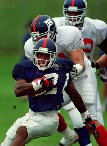 Times Union Staff photograph by Philip Kamrass -- Giants running back Tiki Barber is brought down by linebacker Pete Monty, while linebacker Jack Golden trails the play during practice at Giants training camp at UAlbany Wednesday July 26, 2000. (DG)