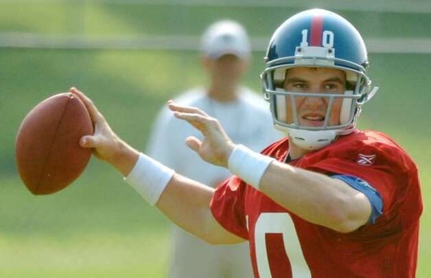 New York Giants quarterback Eli Manning passes during practice at the Giants' training camp at the University at Albany in Albany, N.Y., Friday, July 30, 2004.  (AP Photo/Tim Roske) (AP)
