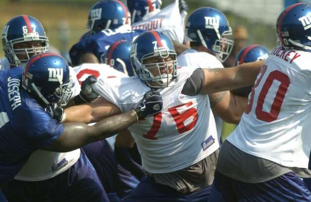 New York Giants guard Chris Snee, center,  blocks players on all sides during the Giants' training camp in Albany, N.Y. Thursday, Aug. 4, 2005. (AP Photo/Tim Roske) (AP)