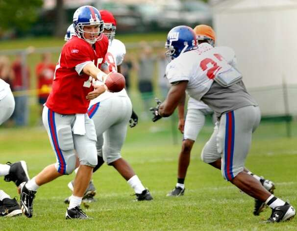 TIMES UNION STAFF PHOTO BY: LUANNE M. FERRIS--Sunday, Aug. 10, 2008, Albany, NY, No. 10, New York Giant QB, Eli Manning, cq., handing off to RB, No. 27, Brandon Jacobs, cq., during evening workout, at 2008 Giant Training Camp held at the University at Albany, on Sunday, Aug. 10, 2008.  GIANT CAMP (ALBANY TIMES UNION)